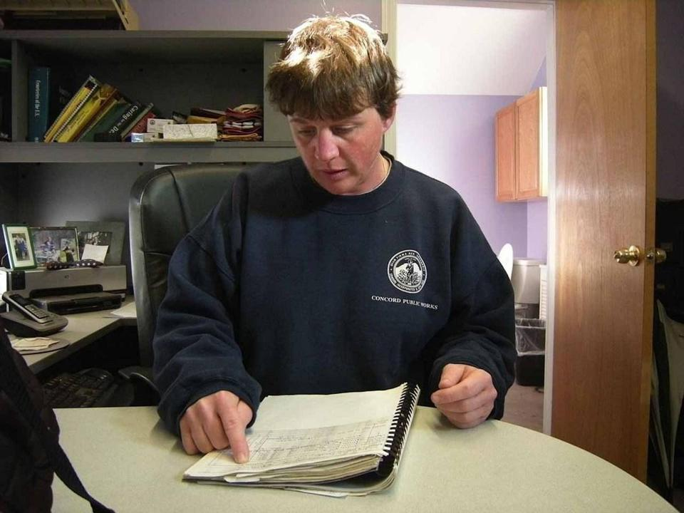 for Globe West - 05weconcor - Cemetery Supervisor Tish Hopkins records burial information on paper. (Betsy Levinson)